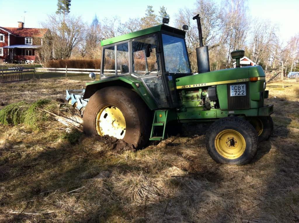 Säker parkering. Härifrån lyckades jag varken köra framåt eller bakåt. Traktorn hänger på bakaxeln med plogen i marken och hjulen vispar leran till ett brund skum när jag försöker förflytta mig.