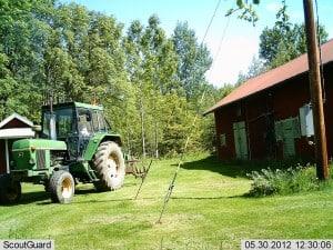 Elegant traktor passerar gårdsplanen med en harv hittad i skogen.