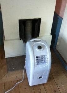 En portabel luftkonditionering kommer till användning några dagar varje år.Men utblåset från luftkonditioneringen in i eldstaden kommer den gamla rörspisen till god användning även så här års.