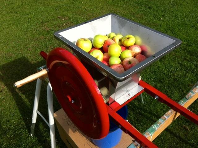 En hink med äpple hälldes i fruktkrossen. Sen var det bara att veva samtidigt som man trycker ner äpplena - och aktar fingrarna.
