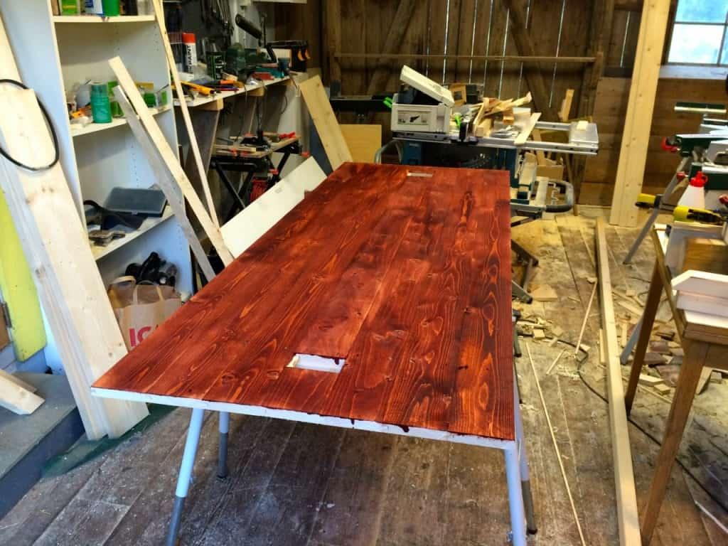 Skivan till mitt marknadsstånd tillverkas av mahogny – eller åtminstone betsad råspont. Lägg märke till de fyrkantiga hålen, där ska stolparna till taket stickas ner.