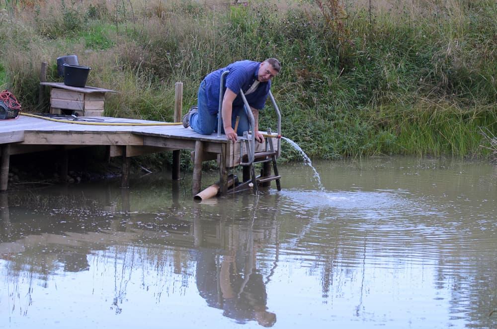 Med tumstock och en fast mätpunkt på bryggan går det att hålla koll på nivån. När vattenståndet i dammen är som högst ligger ytan i nivå med plankan längst ut på bryggan.