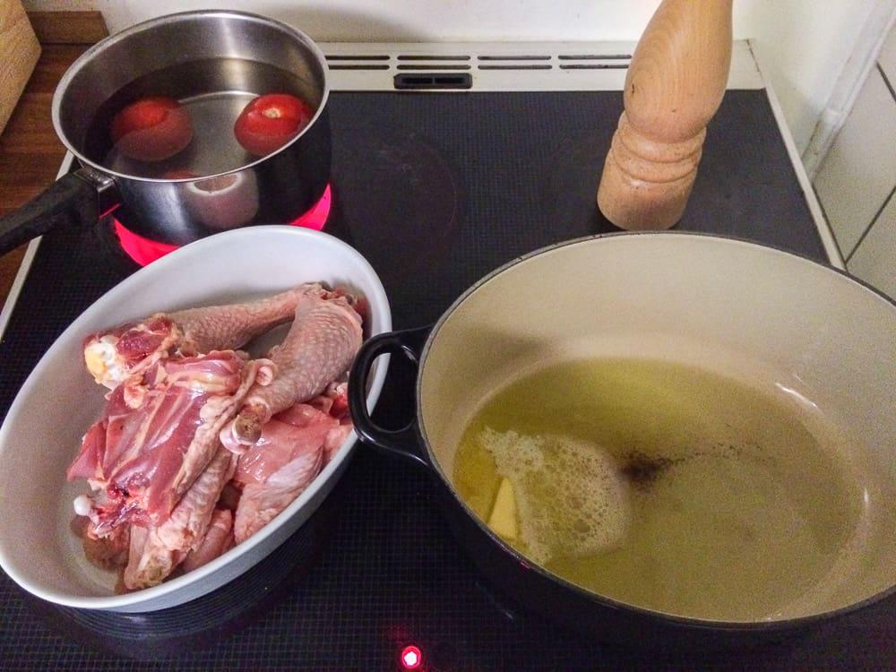 Dela kycklingen i mindre bitar och bryn dem i olja och smör. Därefter tillsätter du löken och efter ett par minuter vinet. Det kan vara bra att börja skålla tomaterna samtidigt. Eftersom jag använder en frigående tupp är köttet betydligt mörkare än den kyckling vi är vana vid,