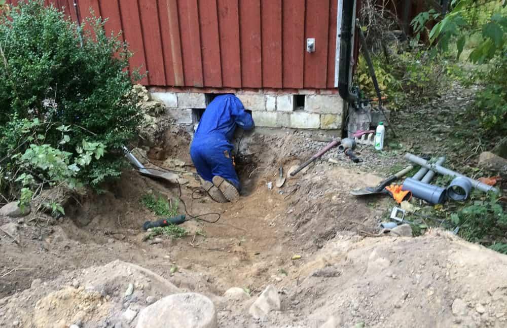Här är gropen som min farbror grävde. Här är min pappa som kopplar rör i gropen som min farbror grävde.
