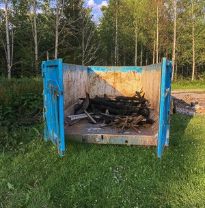 Det blev en del brända stockar kvar av lagården och de får bottna containern som en början av saneringen..